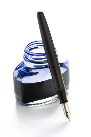 a fountain pen leaning on a bottle of blue ink photo