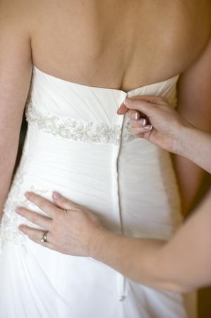 zip tie: bridesmaid zips up the wedding dress of the bride