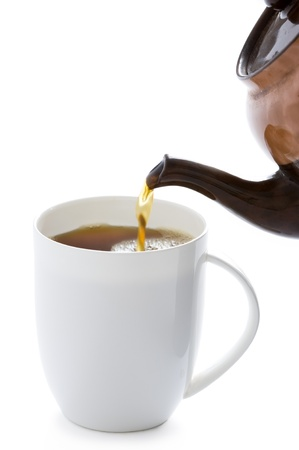 pouring tea from a tea pot into a white cup
