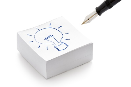 it is isolated: lightbulb drawing on a stack of post it notes illustrating the concept of having an idea