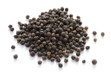 heap of black peppercorns isolated on a white background