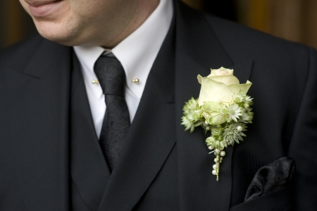 hankerchief: man wearing black suit and floral buttonhole