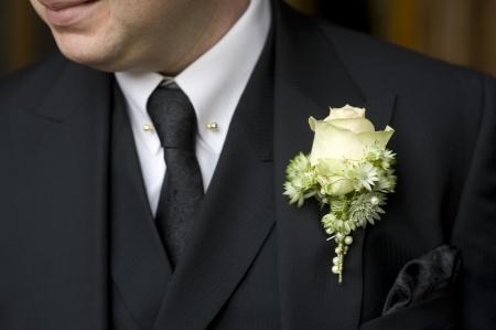 buttonhole: man wearing black suit and floral buttonhole
