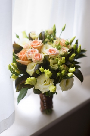 bridal bouquet: wedding bouquet with roses standing on a window sil