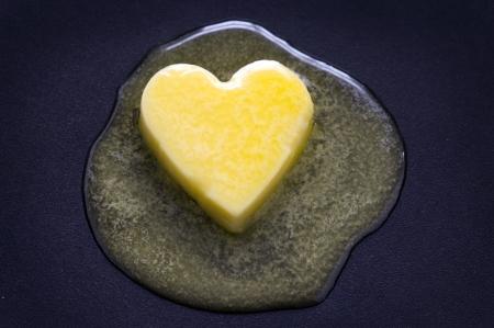 mantequilla: un corazón en forma de mantequilla pat de fusión sobre una superficie no adherente Foto de archivo