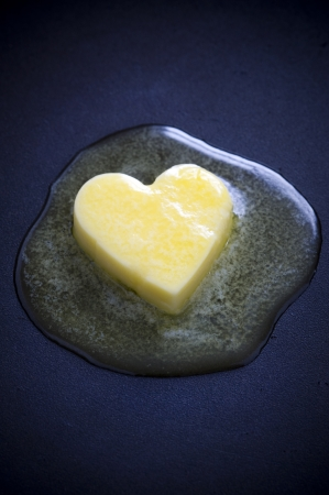 a heart shaped butter pat melting on a non-stick surface photo