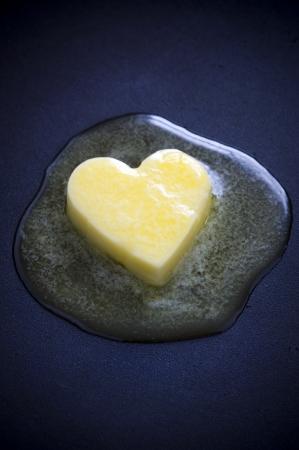 grasas saturadas: un corazón en forma de mantequilla pat de fusión sobre una superficie no adherente Foto de archivo