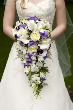 bride holding a large teardrop wedding bouquet