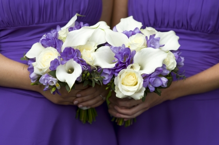 bridesmaids: two bridesmaids in purple with wedding bouquest