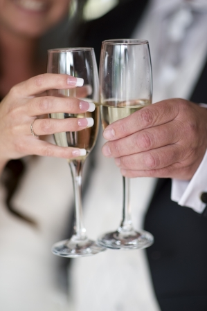 bride and groom hold champagne in glasses for a toast photo