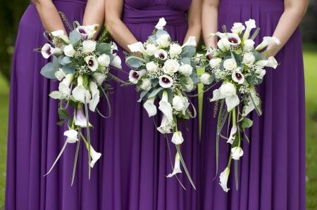 웨딩 부케를 들고 자주색 드레스에 세 신부 들러리