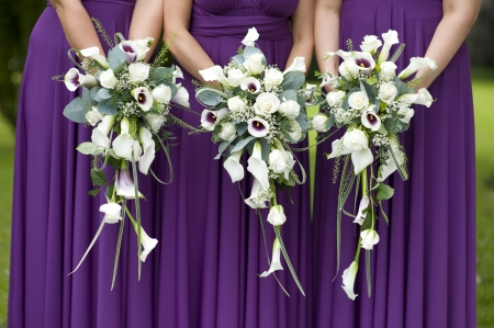three bridesmaids in purple dresses holding wedding bouquets