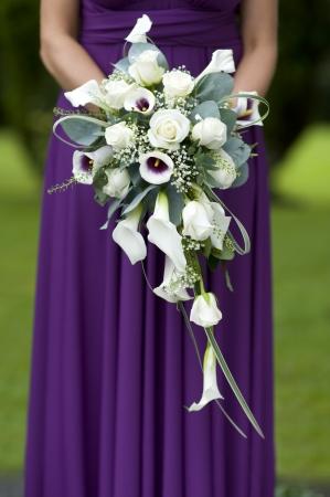 보라색 드레스에 한 신부 들러리는 결혼식 꽃다발을 들고