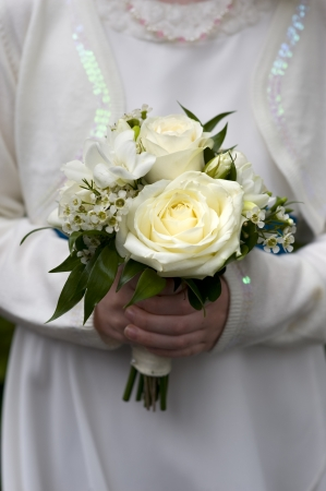 flowergirl: flowergirl or bridesmaid holds bouquet of white roses