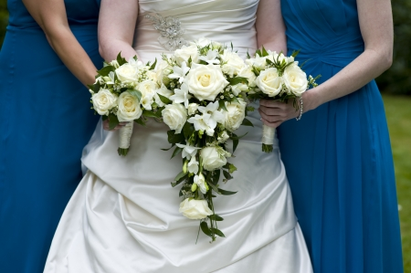 bride and bridesmaids holding wedding bouquets of white roses photo