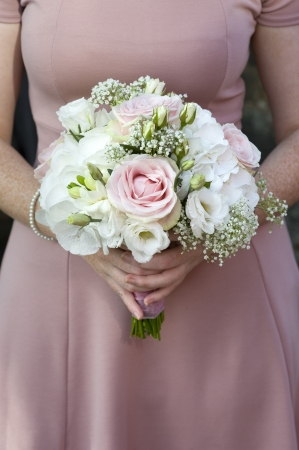 single bridesmaid hold a bouquet of pink and white roses photo