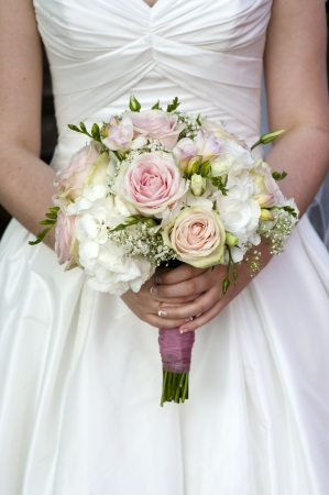 bride holding a bouquet of pink and white wedding flower roses Foto de archivo