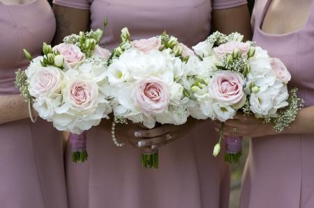 drei Brautjungfern in rosa Kleidern halten Brautsträuße aus weißen Rosen