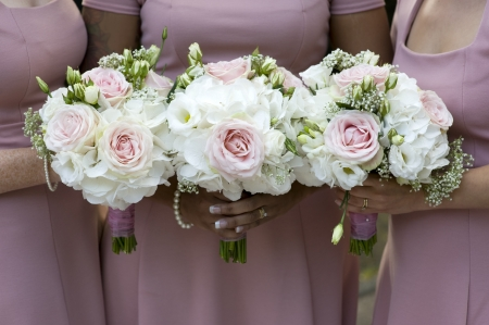 bridesmaid: three bridesmaids in pink dresses holding wedding bouquets of white roses Stock Photo