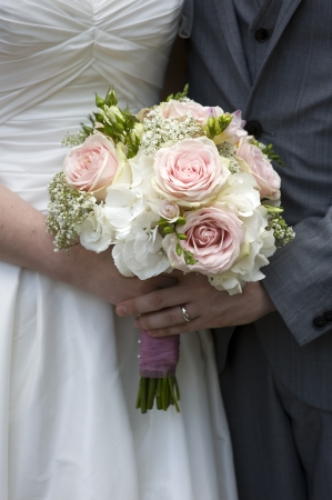 bride and groom with wedding bouquet of white and pink roses