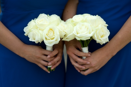 bridesmaids: bridesmaids in blue dresses holding a white rose wedding bouquet Stock Photo