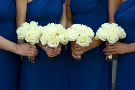four bridesmaids in blue dresses holding a white rose wedding bouquet Foto de archivo