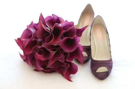 Hochzeit Schuhe und Blumenstrauß der purpurroten Callalilien