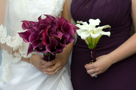 bride and bridesmaid holding bouquets of wedding flowers photo