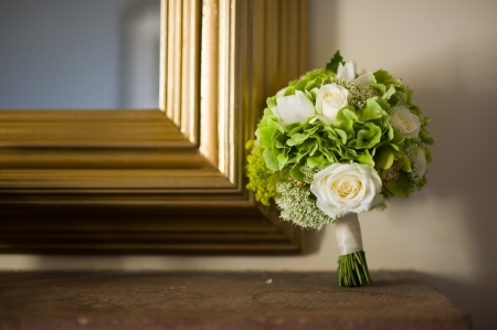 wedding bouquet of white roses with gold frame mirror and shelf photo