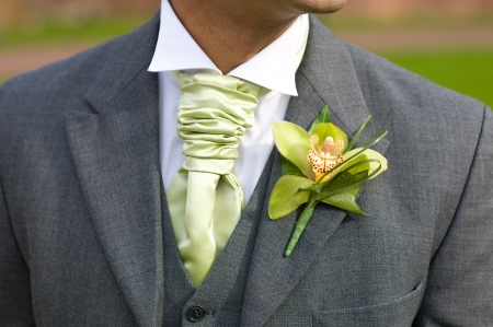 buttonhole: groom with orchid buttonhole and green cravate at a wedding Stock Photo