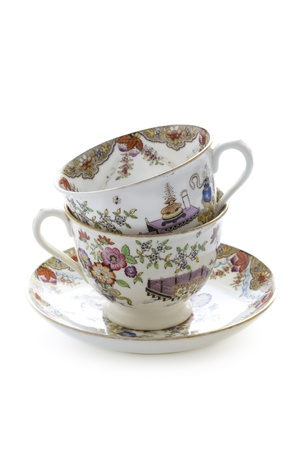 two vintage china tea cups stacked isolated on white Foto de archivo