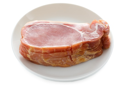 uncooked bacon: pile of raw back bacon rashers isolated on a white background