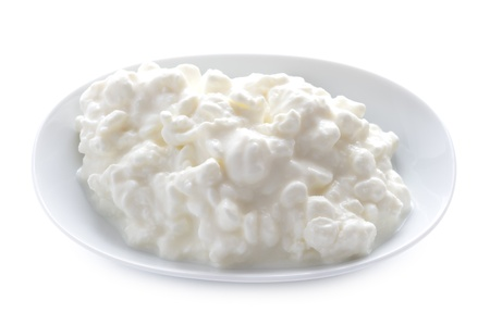 natural cottage cheese in a dish isolated on a white background
