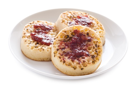 british food: three english crumpets with butter and jam isolated on a white background