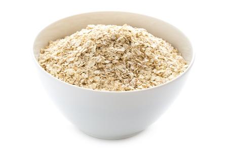 avena en hojuelas: copos de avena seca sin cocer en un recipiente blanco aislado