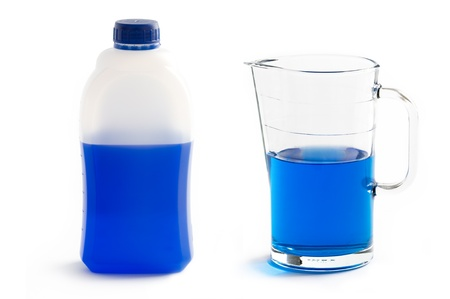 diluted: concentrated liquid screenwash in plastic bottle and diluted in jug isolated