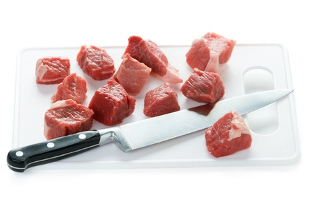 chopping board: raw lamb diced with kitchen knife and chopping board