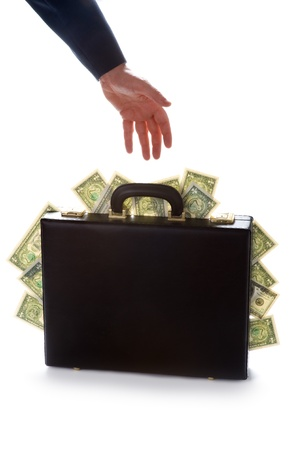 businessman reaching for a briefcase bursting with american dollars photo