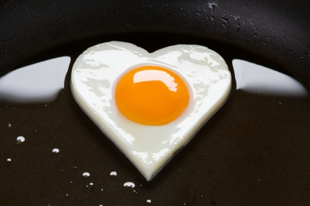 sunny side up: heart shaped egg cooking in a frying pan Stock Photo