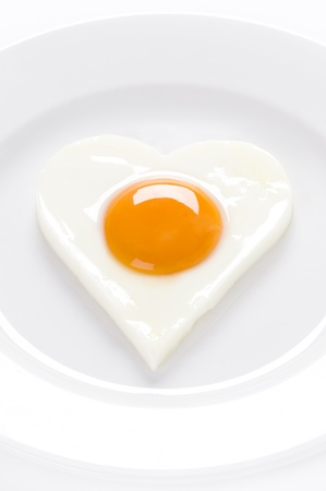 sunny side up: heart shaped cooked egg on a white plate Stock Photo