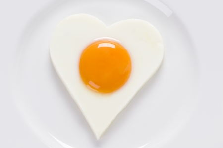 sunny side up: heart shaped fried egg on a white plate from above