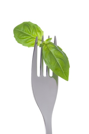 tine: basil herb leaves on a fork against white background