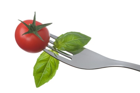 prongs: cherry tomato and basil leaves on a fork against a white background