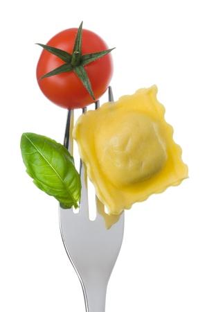 raviolo: ravioli pasta tomato and basil on a fork against white background