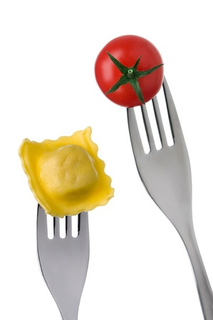 prongs: ravioli and cherry tomato on forks against white background