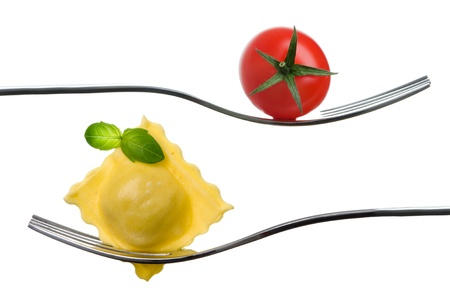 ravioli and cherry tomato on a fork with basil garnish against white background