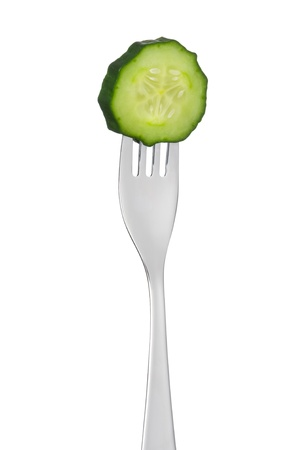 cucumber slice on a fork isolated against white background photo