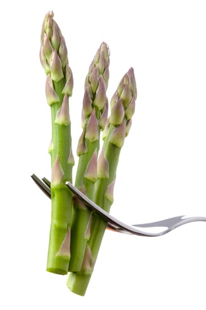 fresh asparagus on fork isolated over white background photo
