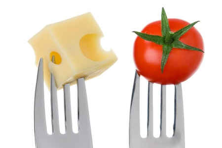 prongs: emmental cheese cube and cherry tomato on forks against white background Stock Photo