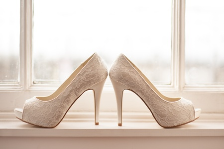 high healed wedding shoes on a windowsill by a window